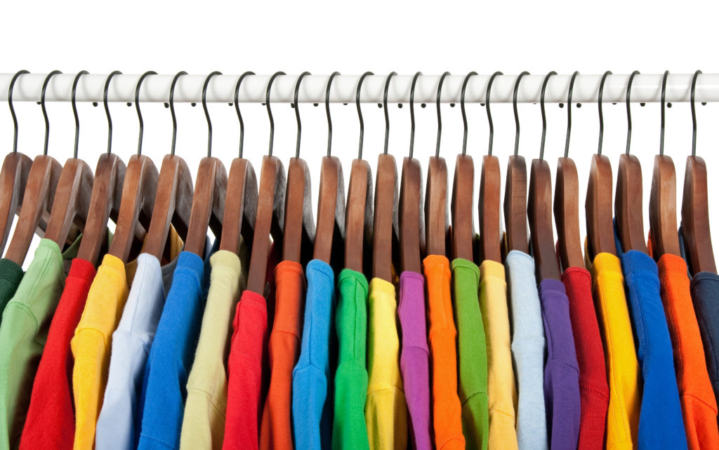 Variety of multicolored casual clothes on wooden hangers, on white background.