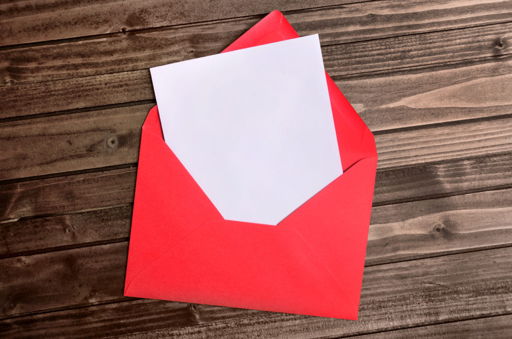 Red envelope with empty paper on wooden table