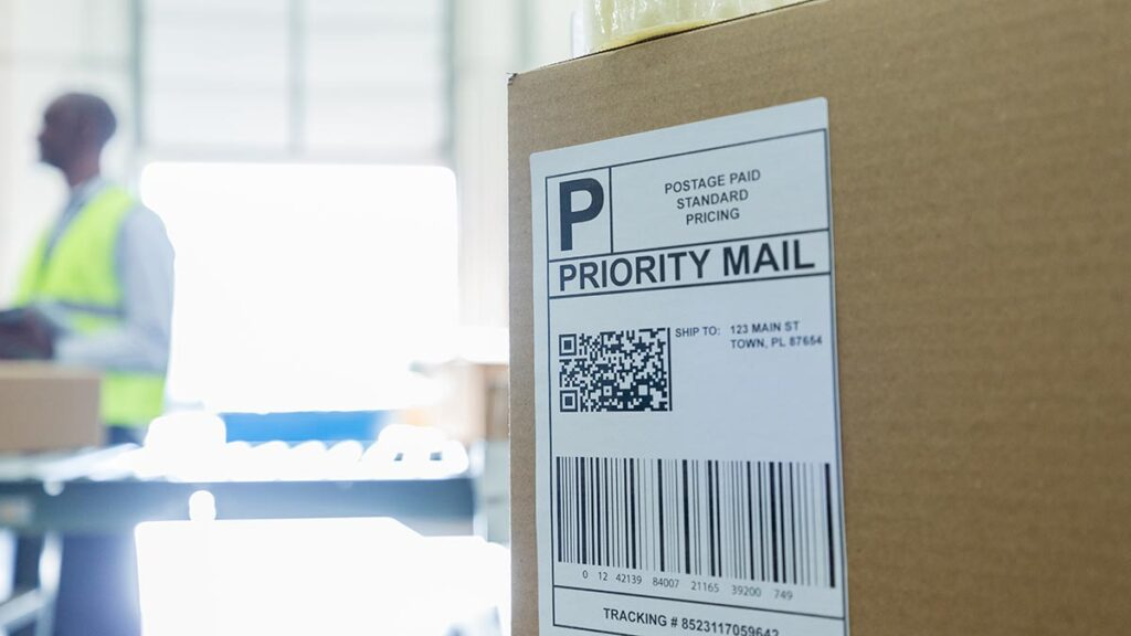 Focus is on a cardboard box in the foreground with a priority mail label.  It is waiting to leave the a warehouse that can be seen in the background.  An employee stands in the background near an open garage door.
