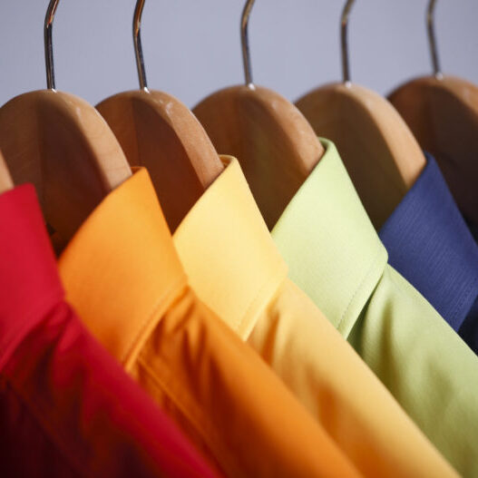 Rainbow colored shirts on hangers.